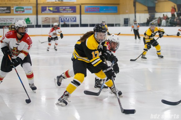 Boston Blades forward Meghan Grieves (17) controls the puck whil being defended by Kunlun Red Stars forward Alex Carpenter (9)
