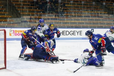The puck is loose in front of the South Korean net