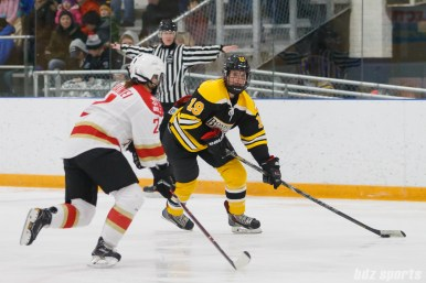 Boston Blades forward Taylor Wasylk (19) looks up ice while being pressured by Kunlun Red Star defender Baiwei Yu (2)