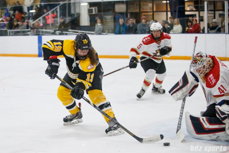 Boston Blades forward Taylor Wasylk (19) redirects the puck towards goal against Kunlun Red Star goalie Noora Raty (41)