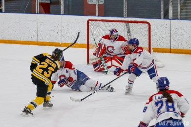 Montreal Les Canadiennes defender Cathy Chartrand (8) slides to block a shot from Boston Blades forward Melissa Bizzari (23)
