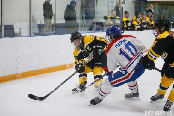 Boston Blades forward Megan Myers (15) controls the puck while being defended by Montreal Les Canadiennes forward Noemie Marin (10)