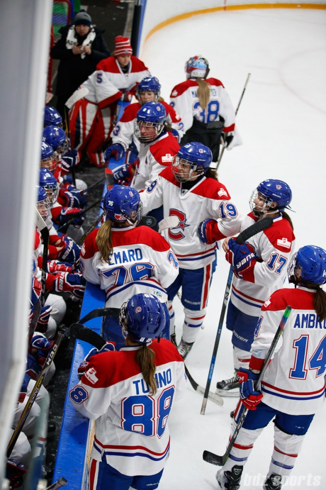 The Montreal Les Canadiennes take a break before the start of overtime