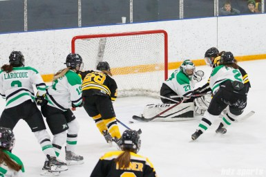 The puck is loose in front of the Markham Thunder goal