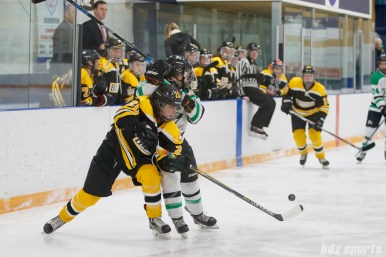 Boston Blades defender Meaghan Spurling (20) reaches around a Markham Thunder player to get her stick on the puck