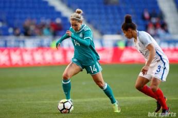 Team Germany defender Anna Blasse (14) takes on Team England defender Demi Stokes (3)