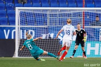 Team Germany midfielder Lena Goessling (8) slide tackles the ball away from Team England forward Ellen White (18)
