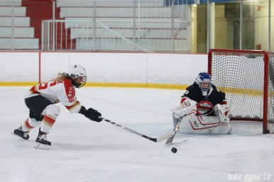Vanke Rays goalie Tianyi Zhang (39) poke checks the puck away from Kunlun Red Star forward Kelli Stack (16)