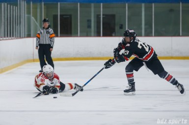 Kunlun Red Star forward Rui Zhu (98) dives to try and get a stick on the puck against Vanke Rays forward Xin Fang (23)