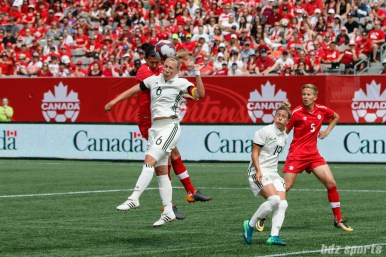 Team Canada forward Christine Sinclair (12) and Team Germany midfielder Kristin Demann (6)