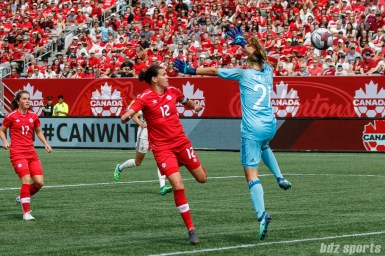 Team Canada forward Christine Sinclair (12) heads the ball past Team Germany goalie Carina Schluter (21) to tie the game