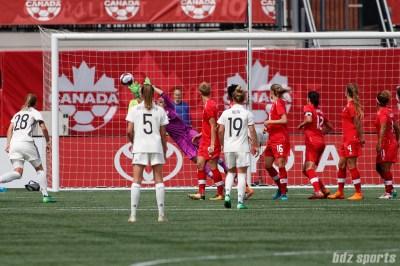 Team Canada goalie Stephanie Labbe (1) gets a hand on the ball