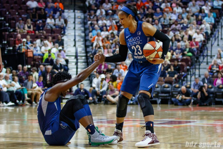 Minnesota Lynx Maya Moore (23) helps up teammate Sylvia Fowles (34)