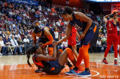 Connecticut Sun players Alex Bentley (20) and Morgan Tuck (33) help up teammate Chiney Ogwumike (13)