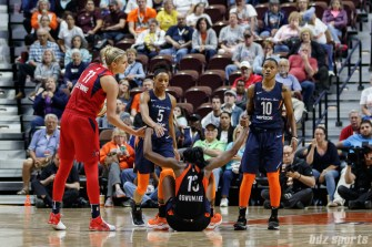 Washington Mystics forward Elena Delle Donne (11) and Connecticut Sun guard Courtney Williams (10) help up Sun forward Chiney Ogwumike (13)