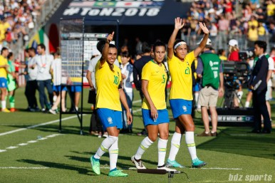 Team Brazil players Marta (10), Thaisa (5), and Monica (21) acknowledge fans after defeating Japan 2-1