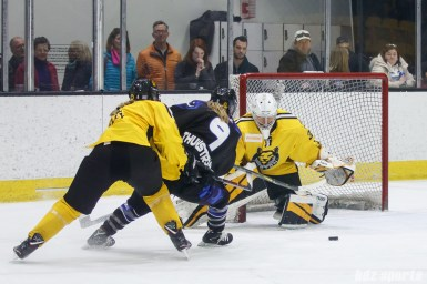 Boston Pride goalie Katie Burt (33) and Minnesota Whitecaps forward Allie Thunstrom (9)