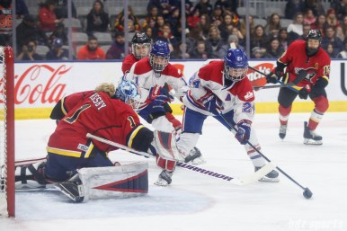 Montreal Les Canadiennes forward Ann-Sophie Bettez (24) and Calgary Inferno goalie Alex Rigsby (1)
