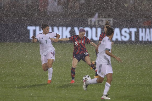 USWNT midfielder Megan Rapinoe (15) and Team Mexico forward Kiana Palacios (9) play in a rainy game in the first of two 2021 WNT Send-Off Series games between the USWNT and Mexico at Rentschler Field in East Hartford, CT on July 1, 2021.