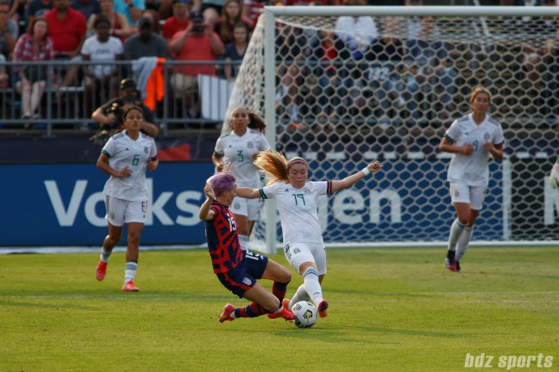 Team Mexico forward Katty Martinez (19) and USWNT midfielder Megan Rapinoe (15) both slide for the ball in the second of two 2021 WNT Send-Off Series games between the USWNT and Mexico at Rentschler Field in East Hartford, CT on July 5, 2021.