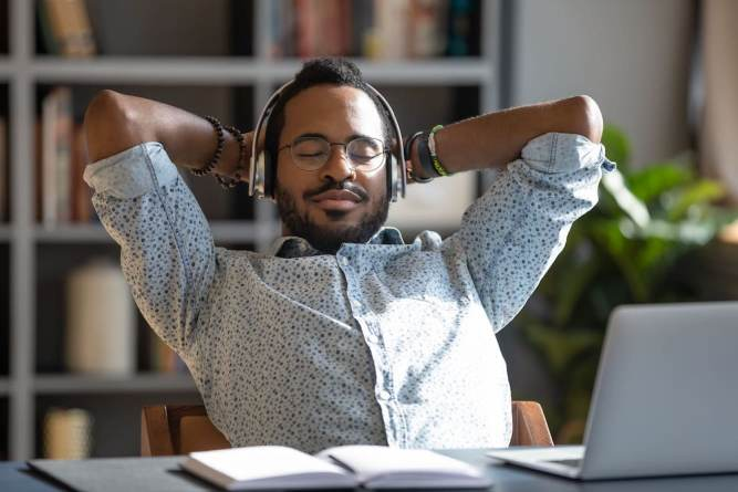 Relaxed guy at desk with headphones on