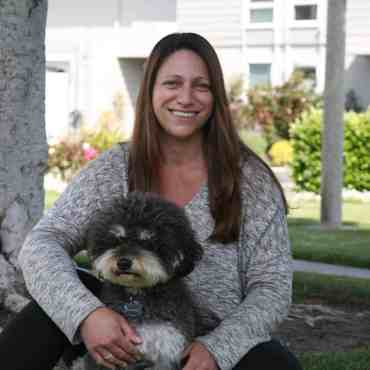 Dr Erin Bukofsky sitting on the ground with a dog