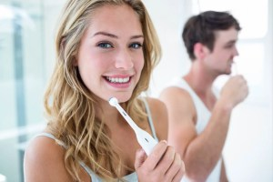 a young couple holding an electric toothbrush