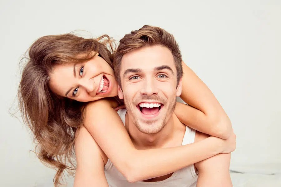 a young couple proudly smiling with their white teeth