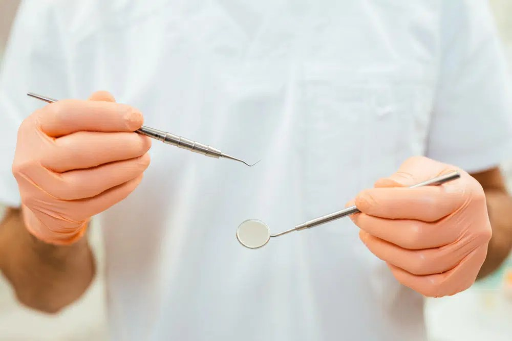 a Mona Vale dentist holding a mouth mirror and a dental probe to prepare for a root canal therapy