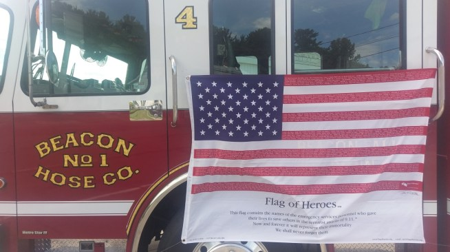 "Beacon Hose's ""Flag of Heroes,"" which includes the names of all the first responders killed on Sept. 11, 2001, hangs from Rescue 4 on Sept. 11, 2016. (Kyle Brennan photo)"
