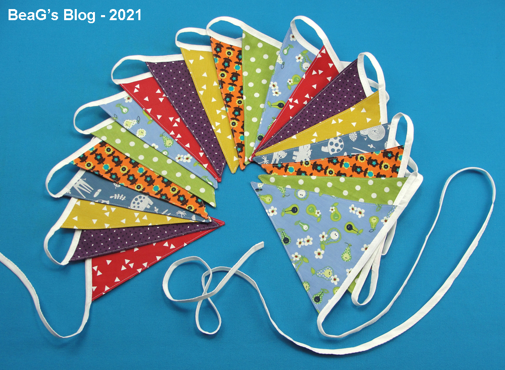 Colorful handmade birthday bunting, laying on blue background.