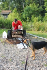 Luna helps set up the grill while camping