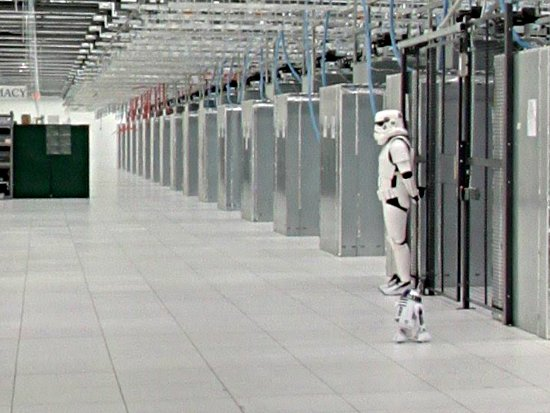 A Google employee dressed as a stormtrooper and a mini R2 unit stand guard inside a Google Data Center.