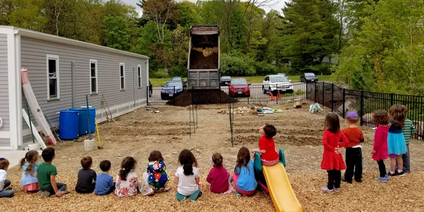 Students watching truck dump soil at Jewish Educational Garden at Striar Hebrew Academy
