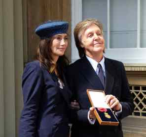 Paul McCartney and Nancy Shevell with his Companion of Honour award, 4 May 2018