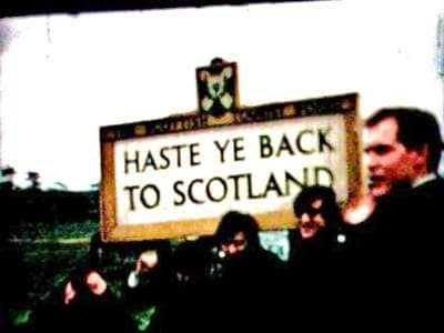 The Beatles beside a 'Haste ye back to Scotland' sign, October 1964