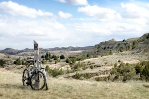 The 1 mile post on the Maah Daah Hey trail and a bicycle resting against it.