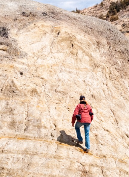 woman hikes up rock wall of a hill in the Badlands of North Dakota.