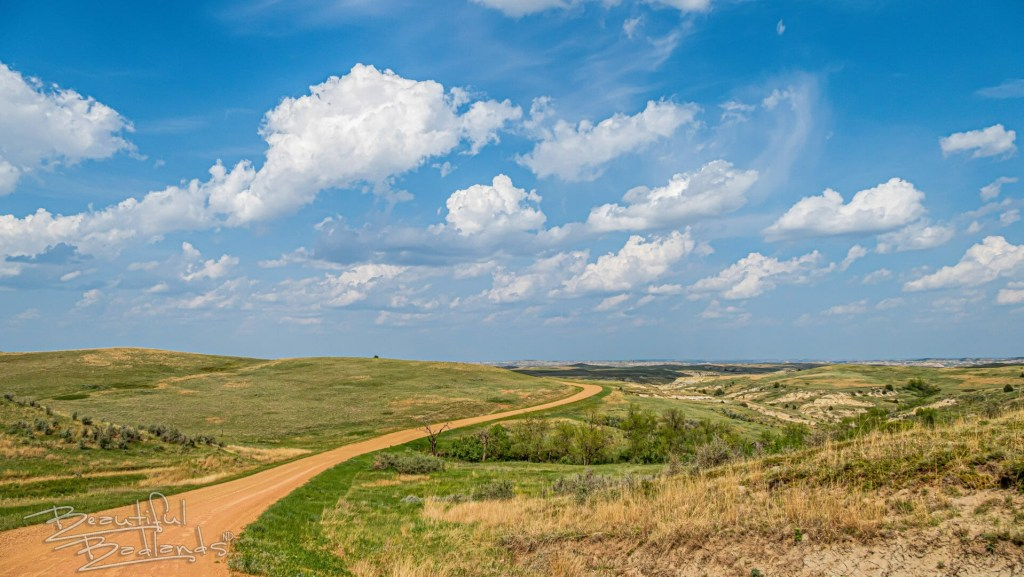 raod through the badlands, blue skies and white cloouds