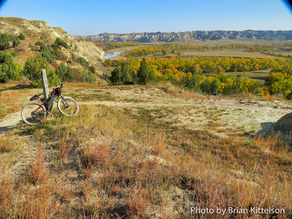Blue skies and brilliant fall colors on the Maah Daah Hey Trail, overlooking the Little Missouri River.