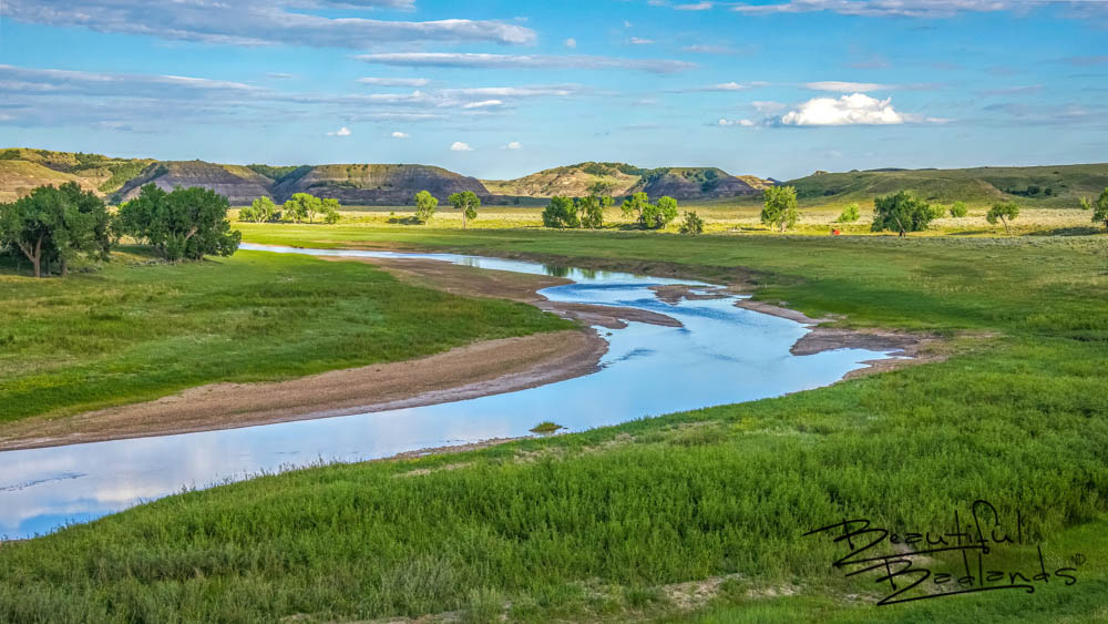 A summer drive on the gravel backroads of western North Dakota, deep in the rugged badlands, skirted the winding Little Missouri River. A short hike brought us to this view of the historic little river. Dreamy. The stillness was hypnotic. The hike was superb! Discover more beauty of western North Dakota here: https://wp.me/p8zmWn-26I Purchase this photo here: http://bit.ly/2Lb6RI2