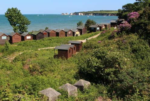 World War II defences, beach huts and Old Harry Rocks, Middle Beach, Studland