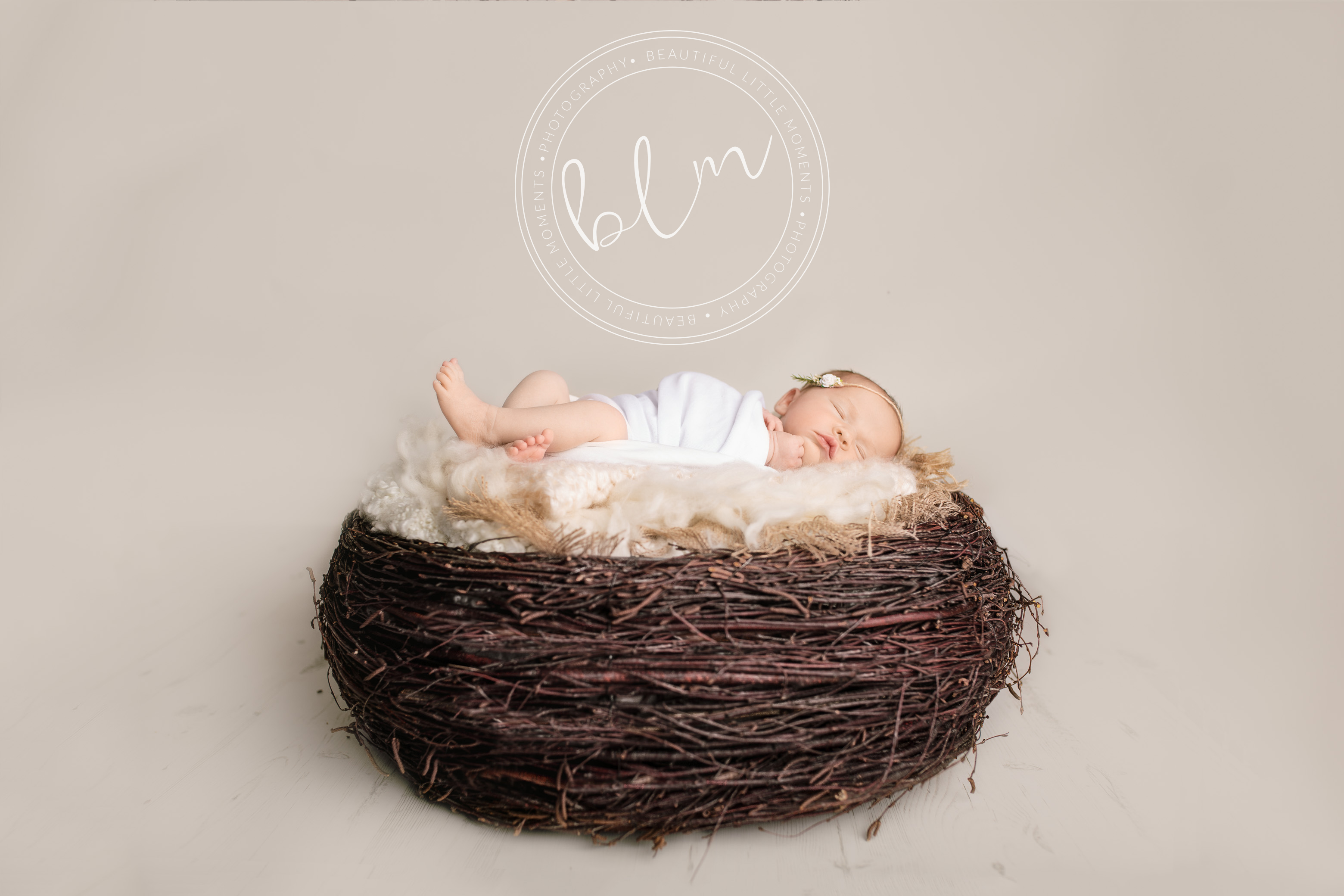 newborn baby girl photo shoot baby wrapped in white in nest