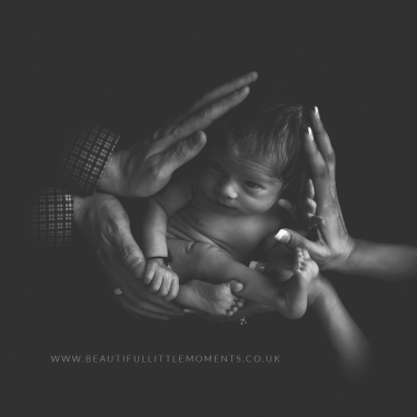 newborn baby girl black and white baby in hands