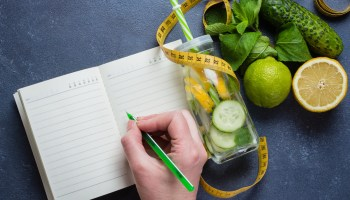 Woman writing nutrition plan diet menu and fitness workout routine. Healthy detox water with lime, lemon, cucumber and mint for slimming down concept. Top view, copy space