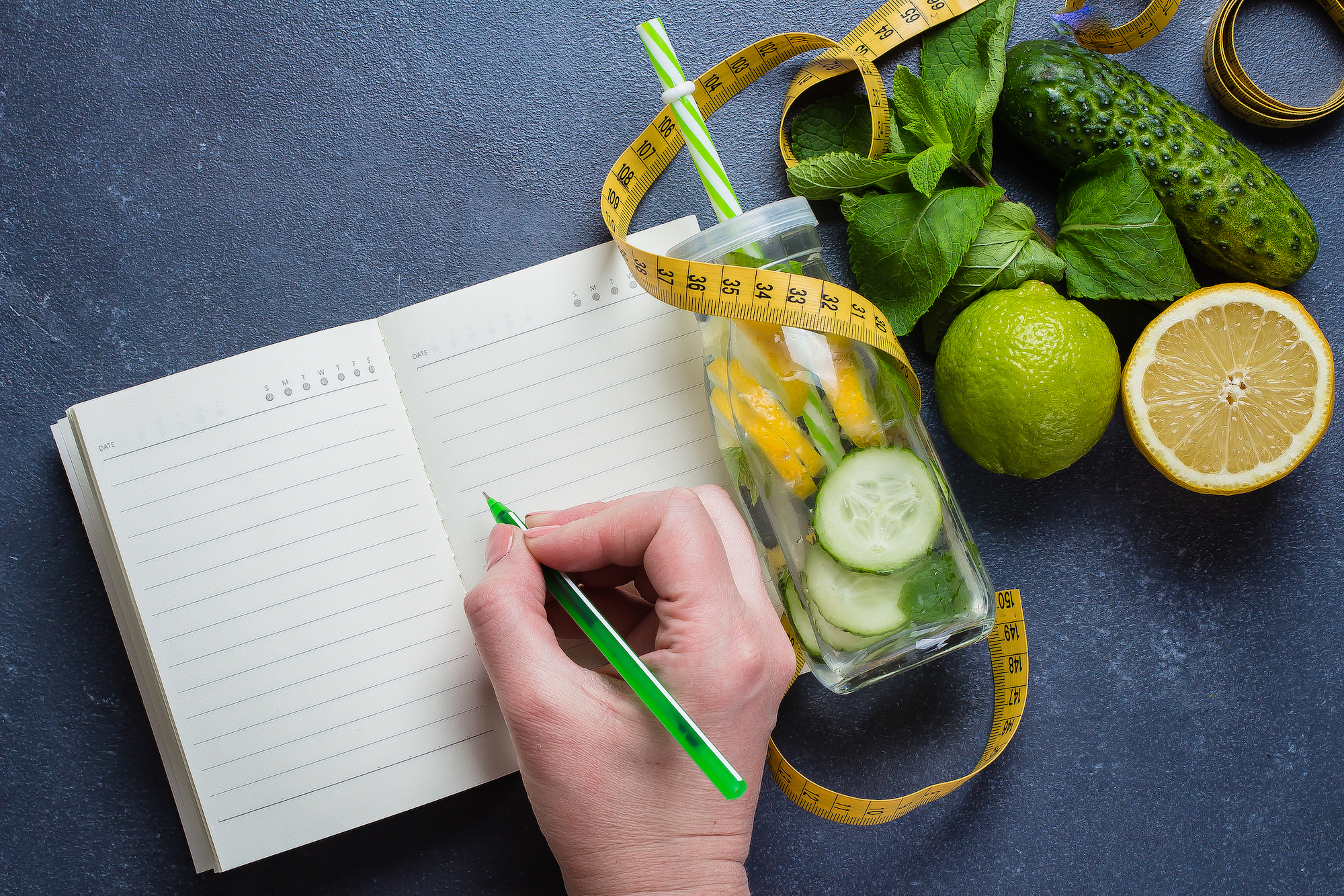 Woman writing nutrition plan diet menu and fitness workout routine.