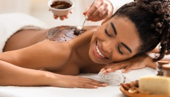 Spa therapist applying exfoliating body mask on happy african woman back at spa, aromatherapty and healing massage procedures concept
