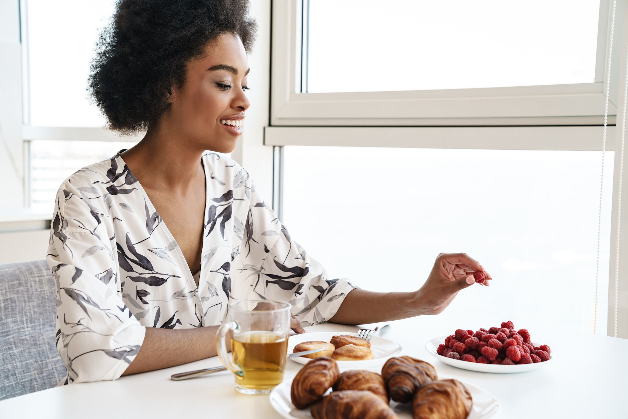 Cheerful beautiful woman having breakfast in kitchen, eating croissants and berries