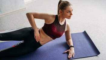 Attractive fit young woman sport wear fitness girl model doing stretching at the home studio workout class