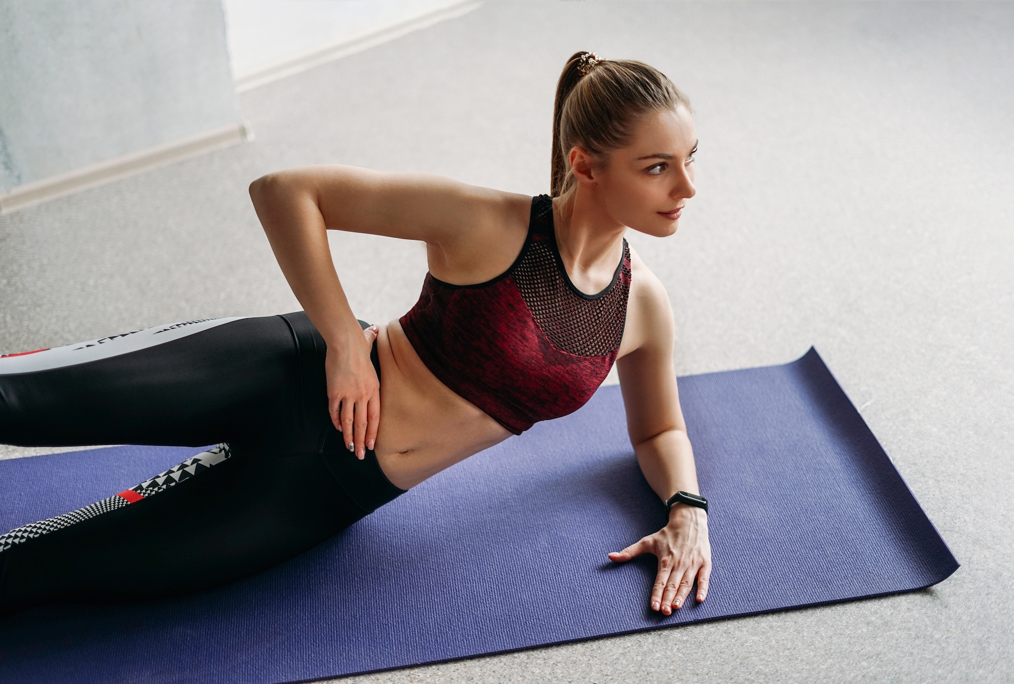 Attractive fit young woman sport wear fitness girl model doing stretching at home studio workout class